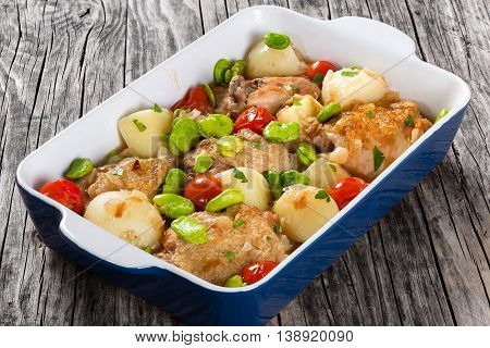 stewed chicken meat new potatoes tomatoes and butter lima bean on graten dish on old wooden table view from above close-up