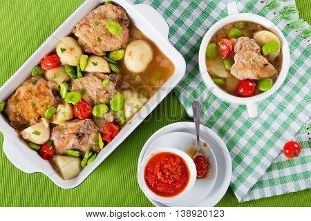 oven baked chicken things new potatoes tomatoes and butter lima bean in graten dish and in soup bowl on table mat view from above