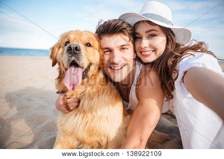 Portrait of happy young couple hugging their dog and smiling on the beach
