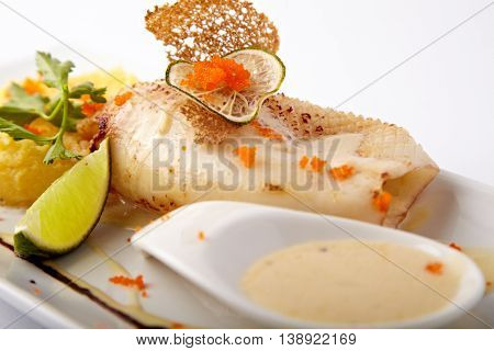 Baked squid with mashed potato and sauce on a white background
