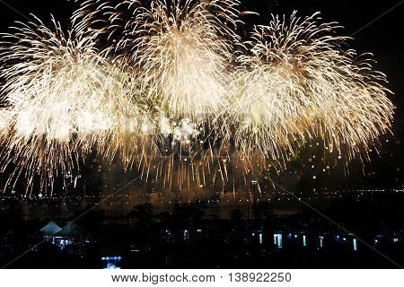 Gold fireworks on the water. International Fireworks. Fireworks display on dark sky background.