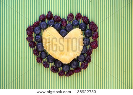Triple heart made of pineapple fresh blueberries and dried cranberries on yellow green stripe background