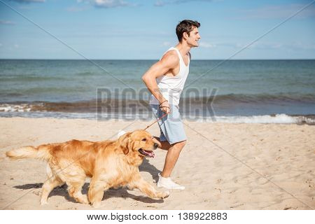 Handsome young man running and having fun with dog on the beach