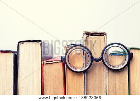 Black round glasses lay on top of a pile of battered old books. Copy space