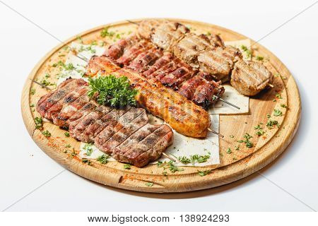 Different kind of grilled meat skewers on the wooden plate on white background