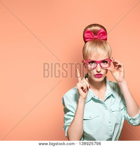Fashion. Woman in Stylish Glasses Having Fun. Hipster fashion girl think, idea. Playful nerd Blonde with Glamour Pinup Stylish hairstyle, Trendy fashion, red bow Makeup. Unusual Creative, on pink