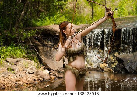 archer shoots a bow on background forest and waterfall