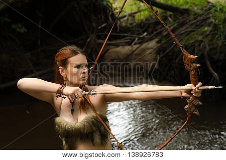 female archer shoots a bow outdoors in forest
