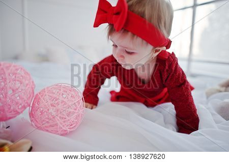 Little Cute Girl In Red Dress Play On Large White Bed