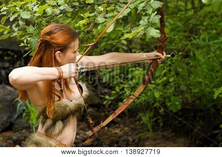 redhead archer shoots a bow outdoors in forest