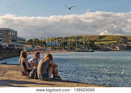 Swanage Dorset UK. July 2016. Teenagers chatting on the pavement of Swanage bay