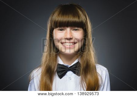 Happy girl. Closeup Portrait of handsome teen in casual shirt smiling isolated on grey background.