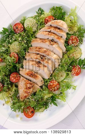 Cut into slices of grilled chicken breast with vegetable garnish