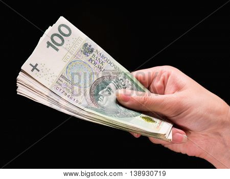 Close up of female hand holding Polish money banknotes against dark background