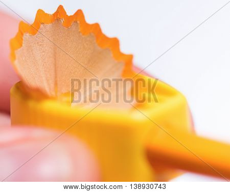 Close up of male hands sharpening a pencil on white background