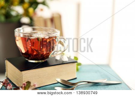 Cup of tea with book on wooden stool