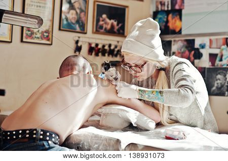 Young Blonde Woman Master Tattooist In Glasses And Hat With Tattoo Machine At Hands Make Tattoo Drea