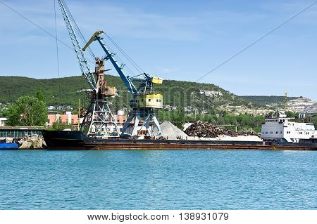 Cargo ship docked for loading in old harbor. Plenty of cargo ships needs oil and equipment for the long journey by sea.