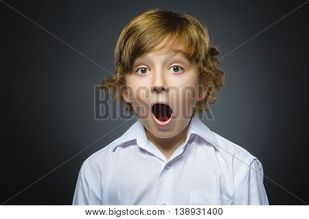 Closeup Portrait of handsome boy with astonished expression while standing against grey background.