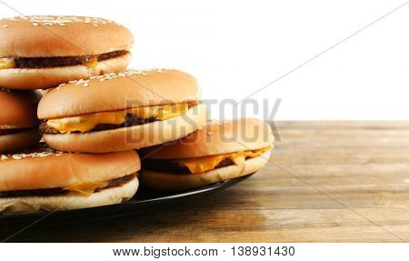 Tasty cheeseburgers on plate, isolated on white