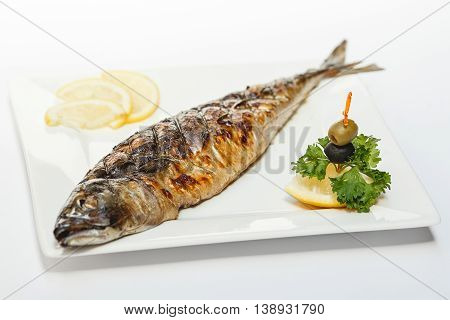 Baked whole fish grilled on a plate with lemon on white background for the menu
