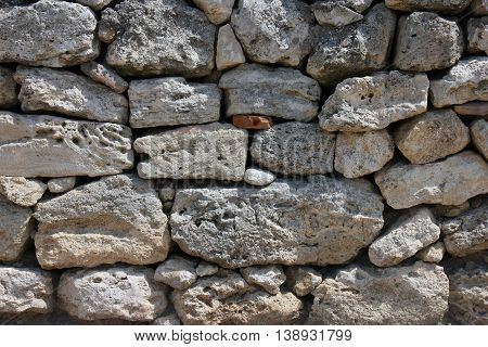texture of old dilapidated shabby sandstone masonry of wild natural sandstone stones wall foreground closeup in Crimea