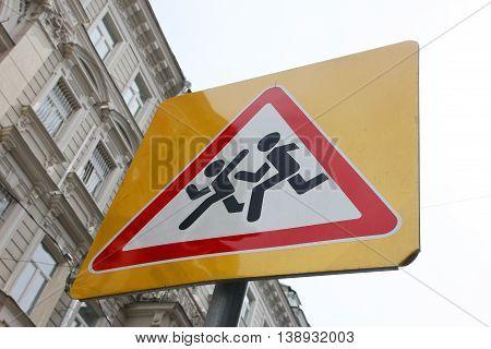 triangular road sign Children on yellow background on city street closeup