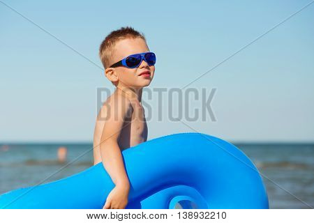 Child Is Going To Swim In The Sea With Swimming Mattress.