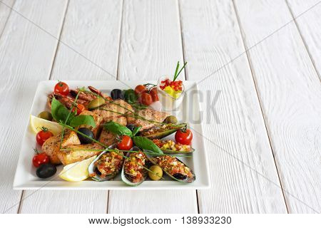 Seafood snack on white wooden background. Closeup of plate with grilled shrimps, salmon and stuffed mussels. Copyspace for text or advertising