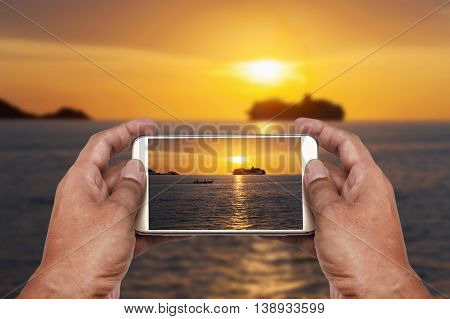 Hand with phone on blurred dramatic sea and transport boat with color of sunset and over light the sun in twilight