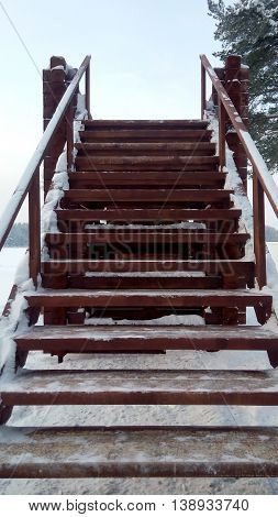The wooden stairs on the winter hill