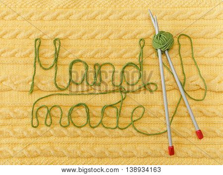 Yellow Knitted Background with Pattern and Braids;Grey Knitting Needle and Green Ball. Hand Made; Fancywork.Sign Hand-made from Thread