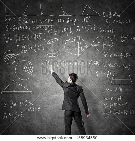 Man in suit standing with back and drawing formulas on chalkboard