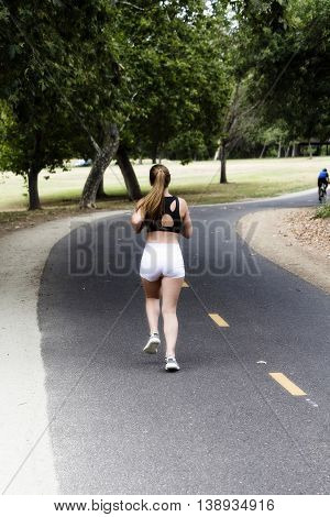 Caucasian Teen Woman Running On Bike Path Away From Camera Pony Tail Black Top White Shorts
