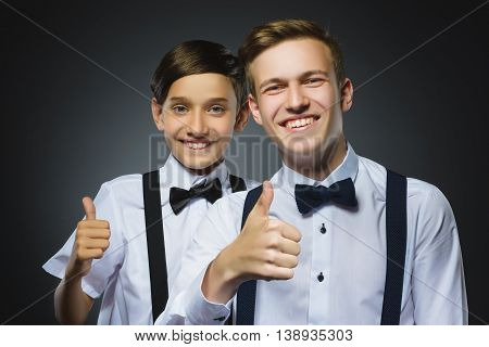 Closeup portrait of two successful happy boys show thumbs up isolated grey background. Positive human emotion