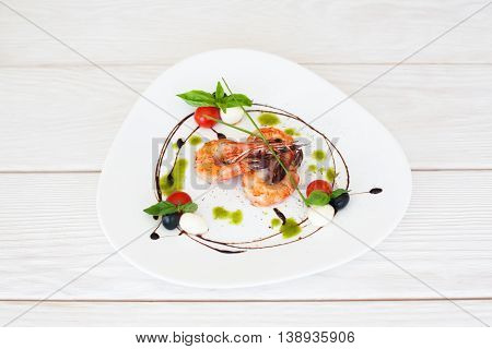 Plate of fried prawns on white wooden background, free space for text, top view on served seafood meal, photo for menu