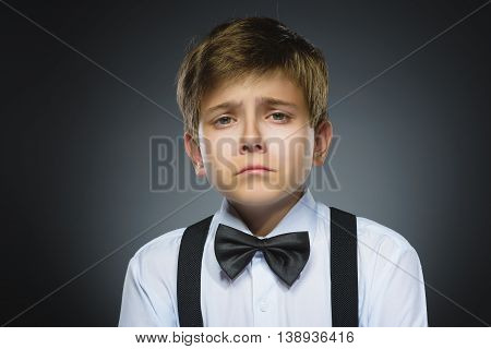 Portrait of offense crying boy isolated on gray background. Negative human emotion, facial expression. Closeup.