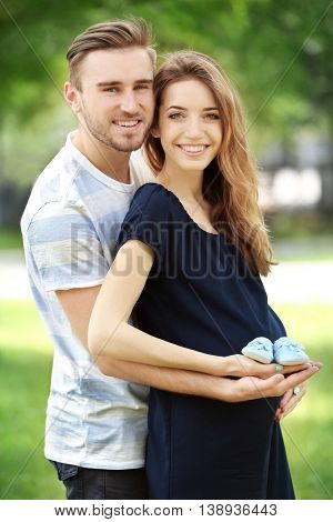 Happy family holding baby shoes on green nature background