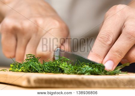 hands chopping fresh dill on the wooden cutting board