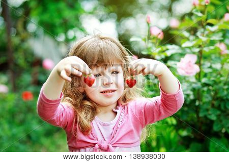 little girl play with fresh strawberry on  nature backgraund