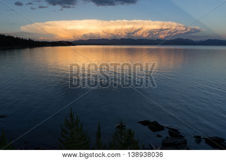 A large cloud mushrooms out over the mountains surrounding Yellowstone Lake
