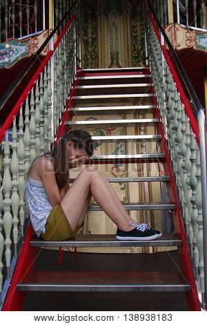 Portrait of sad little girl sitting on stairs at the day time.