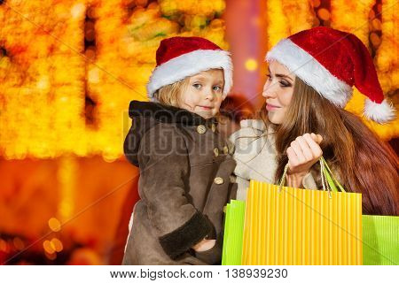 Mother looking at her beautiful daughter and holding paper bags with New Year gifts