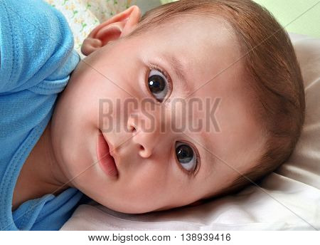 Beautiful little baby portrait,lying down on bed,smiling.