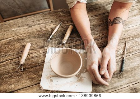 Tired potter hands near pottery on wooden table flat lay. Short break in creation, waiting for inspiration