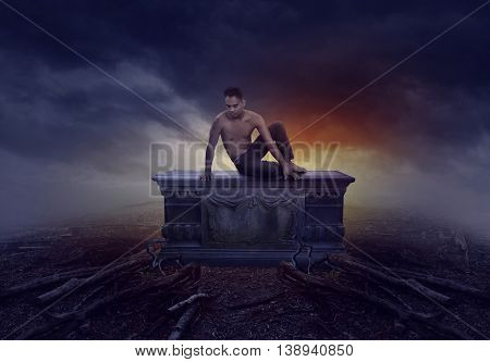 young man sitting on a grave next to a cloudy sky