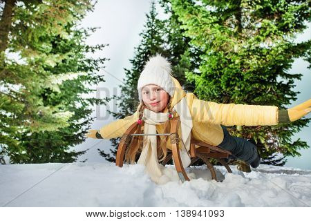 Child girl riding a sledge outdoors in snowy forest