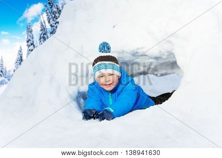 Happy smiling little boy lay in the snow tunnel wearing colorful blue clothes and hat