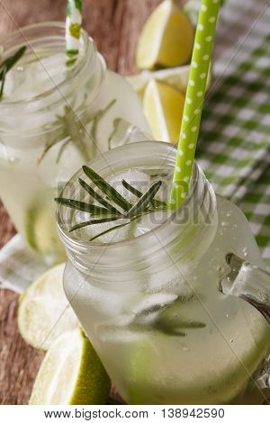 Refreshing Drink With Lime, Ice And Rosemary Macro In A Glass Jar. Vertical