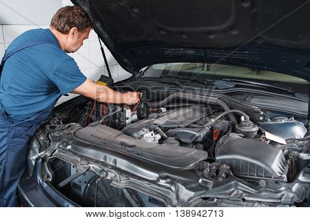 Electrician testing car electronics with multimeter at garage. Repairman working with automobile inside with electrical tester in his hands.